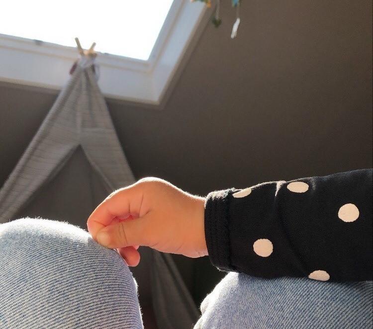 Eine Kinderhand liegt auf einem Knie.