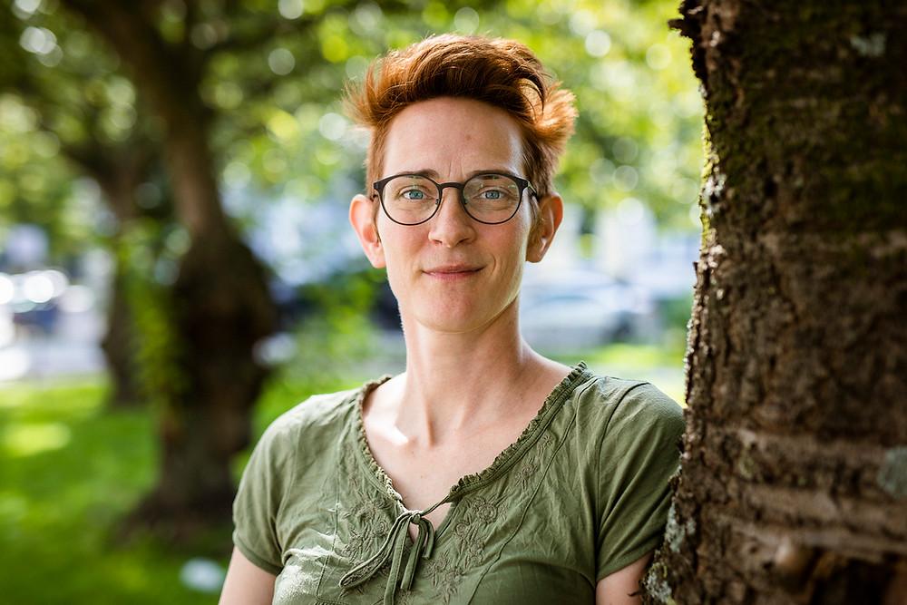 Leena May Peters hat rote, kurze Haare und eine Brille. Sie steht neben einem Baum und schaut lächeln in die Kamera.