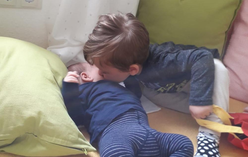 Ein Baby liegt auf dem Bett, sein älterer Bruder küsst es auf die Wange