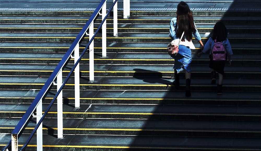 Mutter läuft mit Kind an der Hand Treppen hoch. Sie in der Sonne, das Kind im Schatten