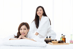 Beautiful Asian woman massages her friend in a home spa treatment
