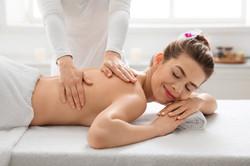 Unrecognizable female massage therapist rubbing young woman back, spa salon interior, empt