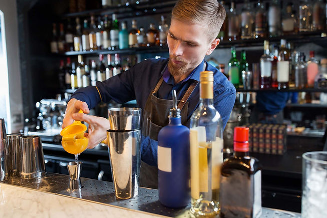 barman-with-shaker-alcohol-and-jigger-at