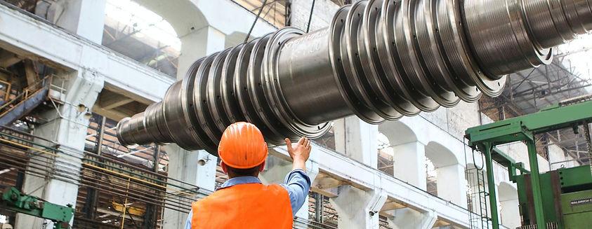 Ein Arbeiter mit Helm in Industriehalle gibt Anweisungen für Kran, der eine Stahlwelle transportiert.