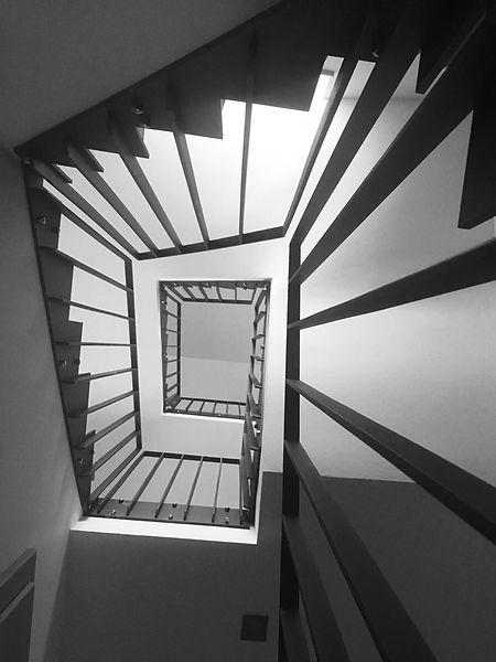 Ein Stiegenhaus mit klassischem Geländer in Schwarz