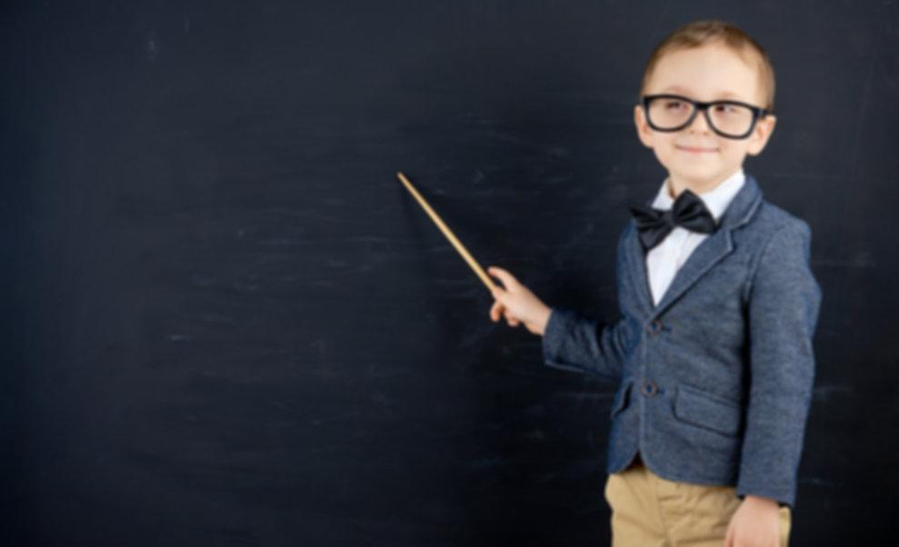 Little boy against blackboard. School co