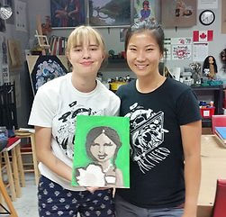 Camper holds a portrait painting that she created at summer art camp.