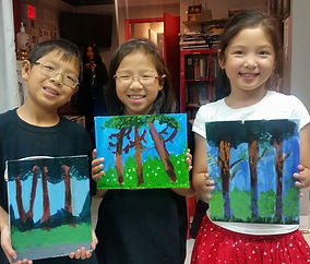 Three kids hold up paintings they created at a PA Day Painting Camp