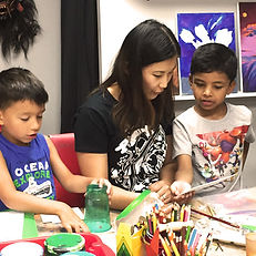Art teacher showing techniques to two young boys