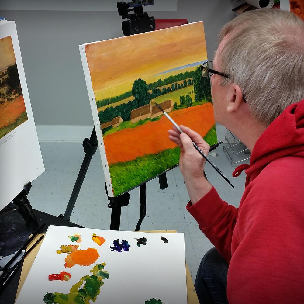 man painting a landscape using oil paints