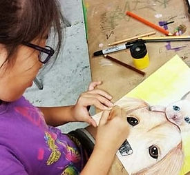 Art student drawing a dog and cat in coloured pencil
