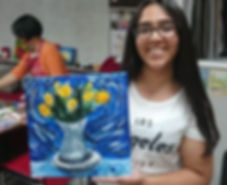 Teen girl smiling and showing her acrylic painting of flowers.