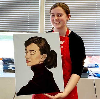 Student proudly shows her oil painting portrait of Audrey Hepburn