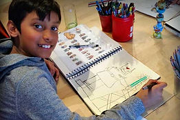 A boy shows his drawing of a cartoon robot