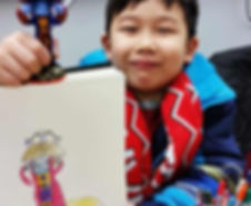A boy holds up a drawing he made in Beginner Drawing Class