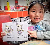 little girl smiling and holding cartoon drawing
