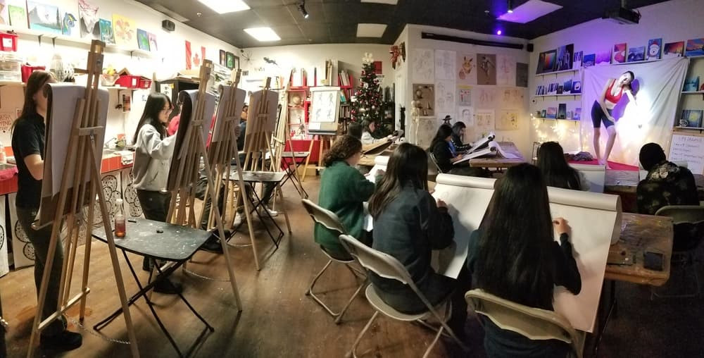 A wide shot of a group of grade 11 and 12 students. All are participating in a life drawing session.