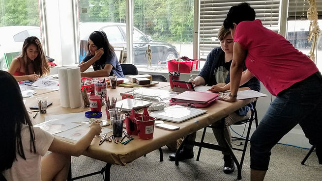 Teens work on their drawing skills with a Winged Canvas Instructor at a Teen Art Camp