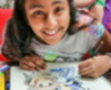 A smiling girl is drawing an anime style cartoon