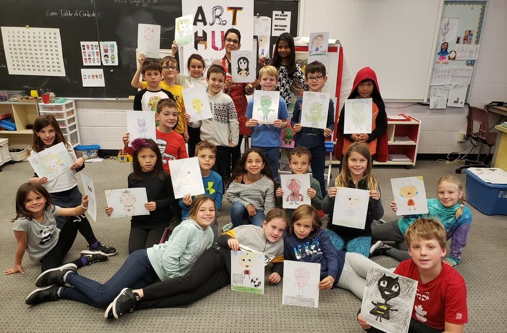 A group of 21 3rd grade students all hold up their artwork, smiling at the camera along with an art instructor in the back.