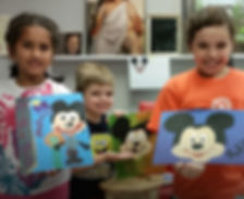Three kids hold up paintings they created at Winged Canvas in Beginner Art for Kids class