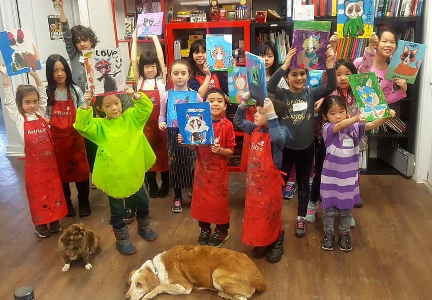 Kids at Art Camp pose with their artwork and the studio dogs.