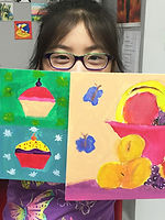 A girl holds up her colourful paintings