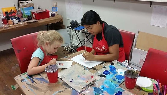 Art teacher working one on one with a young student