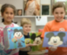 three kids holding paintings they made at Winged Canvas Art Hub