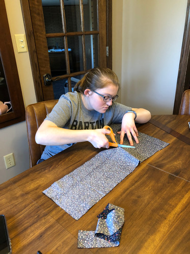 Hannah Evers Cutting fabric for masks.JP