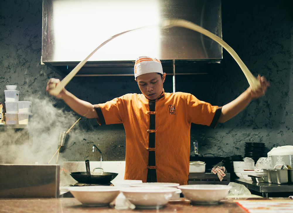 A Cook being sponsored on a TSS visa by his restaurant, preparing asian food in the kitchen