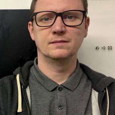 Simon standing next to his self portrait