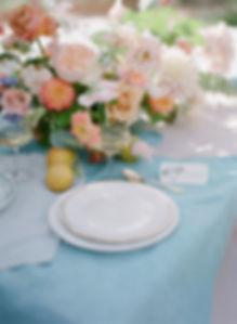 Table setup including tableware, floral arrangement and stationery
