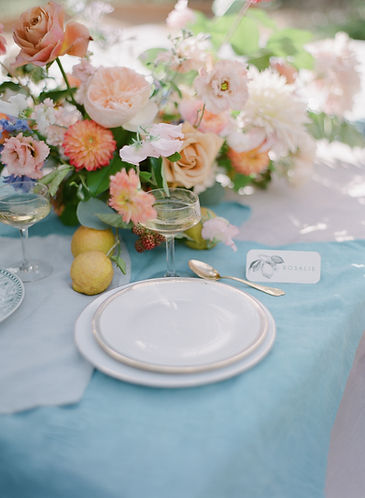 Table setup including tableware, floral arrangement and stationery