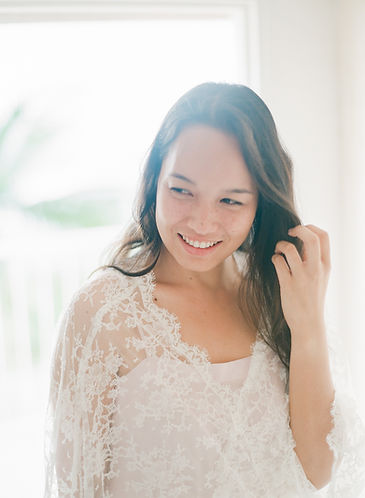 Close-up on a smiling pretty girl wearing a lace kimono and playing with her hair