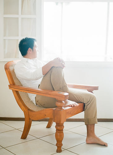 A man in chino sit on a chair and looking outside
