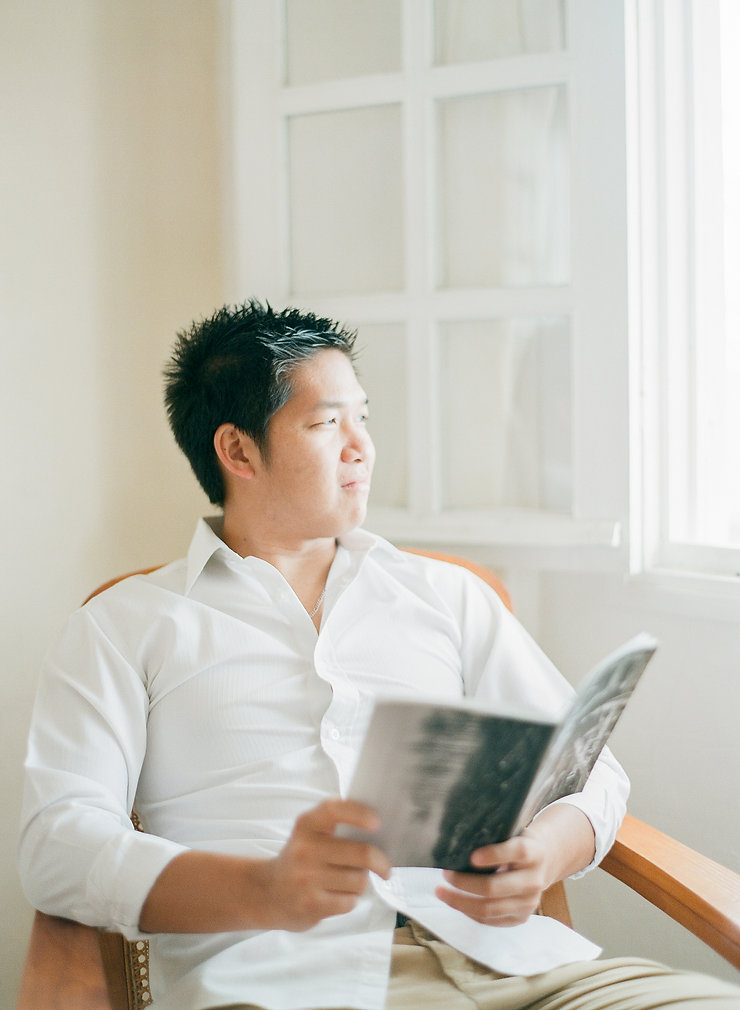 Close-up on a man holding a book and looking outside throught a window