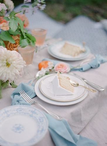 Picnic table setup with a part of wedding cake