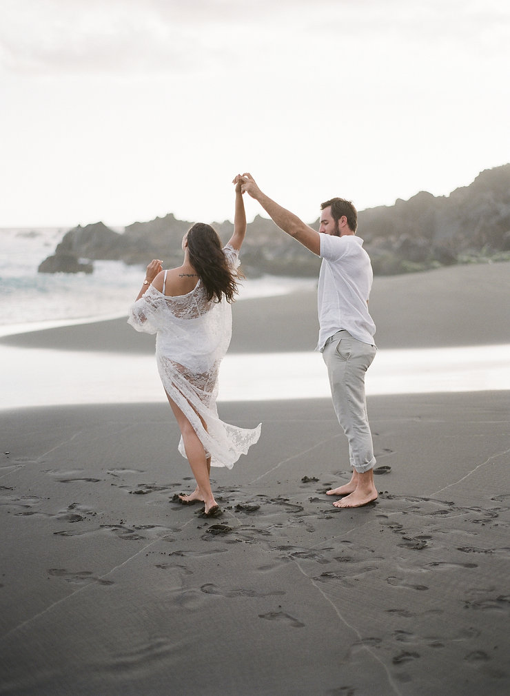 Girl and boyfriend dancing on a black sand beach