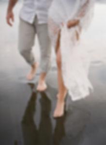 Girl and boyfriend strolling on a black sand beach