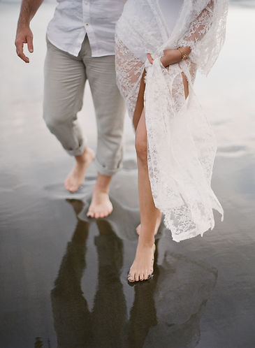 Girl and boyfriend strolling on a black sand beach