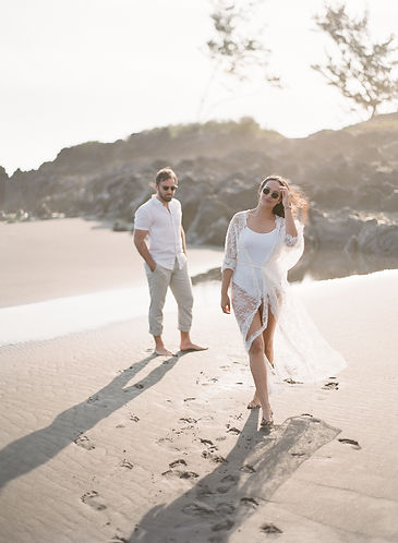 Girl and boyfriend walking on a black sand beach