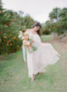 Bride to be in holding a bouquet, smiling and playing with her dress