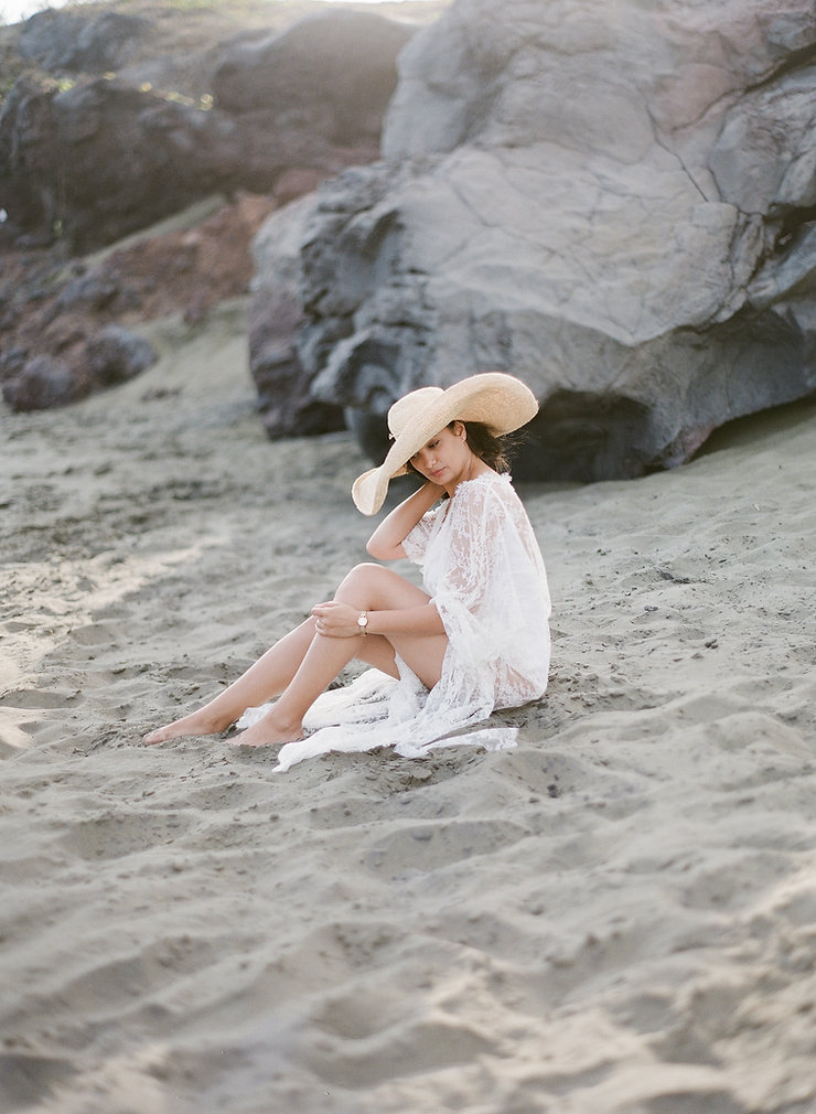 Girl in a lacy kimono seating on a black sand beach