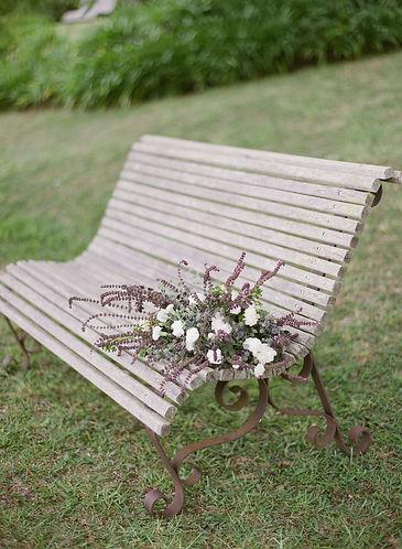 A bouquet on a garden benc