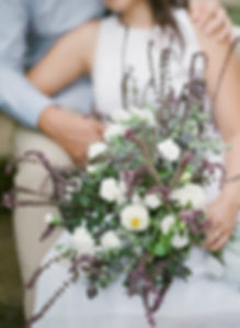 A coupl of lovers sitting down on stairs and holding a bouquet