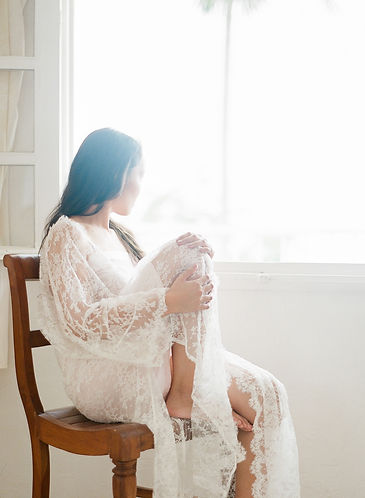 Pretty girl on a chair wearing a lace kimono looking outside throught a window