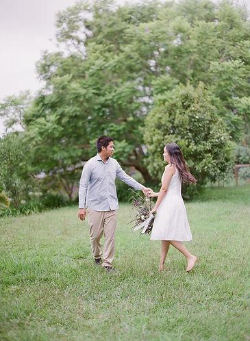 A man making his girlfriend spin in a garden