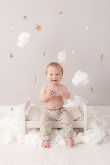 Garçon assis dans les nuages et les étoiles