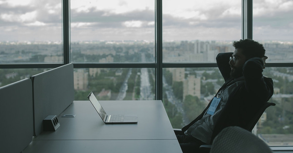 man looking at laptop in top view office building
